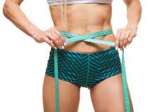 Sportowa szczupła kobieta mierzy jej talię miarą taśmy po diety nad czarnym tłem Obrazy Stock