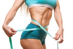 Sportowa szczupła kobieta mierzy jej talię miarą taśmy po diety nad czarnym tłem Zdjęcia Stock