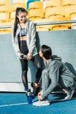 Sportowe młode kobiety w sportswear wodzie pitnej od sport butelek na stadium Fotografia Royalty Free