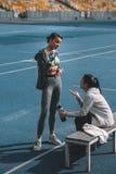 Sportowe młode kobiety w sportswear wodzie pitnej od sport butelek na stadium Obrazy Royalty Free