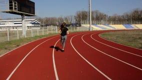 Sportowej dysponowanej młodej atrakcyjnej kobiety działający maraton jogging w zwolnionym tempie, plenerowy stadium trening na po zbiory wideo