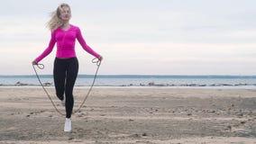 Sportowej dziewczyny skokowa arkana na piaska morza plaży Sprawność fizyczna w natura chmurnym dniu zbiory wideo