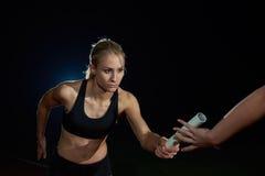 Sportowi biegacze przechodzi batutę w sztafetowej rasie Fotografia Stock