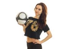 Sportowi młoda dziewczyna stojaki z piłki nożnej piłką, utrzymywać jego rękę na stronie i fotografia stock