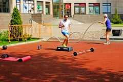 Sportowi młodzi człowiecy robi niektóre crossfit ćwiczą z arkanami outdoors obrazy stock