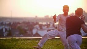 Sportowi silni mężczyzna trenują, machający ich ręki na trawie i nogi przeciw zadziwiającemu zmierzchowi zbiory