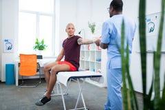 Sportowiec opowiada jego fizyczny terapeuta podczas gdy robić ćwiczy zdjęcie royalty free