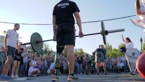 Sportowiec upośledzający z sztucznej nogi podwyżek barem nad głowa przed tłumem ludzie zbiory