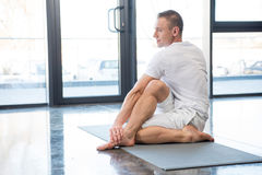 Sportowiec w przyrodnim dordzeniowym skręt pozy obsiadaniu na joga macie fotografia stock