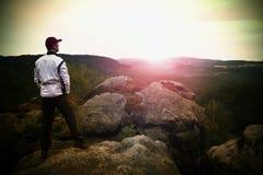 Sportowiec z czerwoną baseball nakrętką w białej kurtce na skalistym szczycie i Marzycielski fogy krajobraz, piękna dolina below Zdjęcia Royalty Free