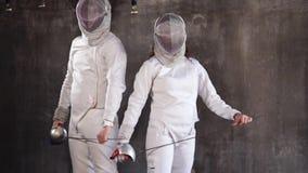 Sportowowie w fechtunku nadają się z maskami na twarze i kordziki w ręki w sala zbiory wideo