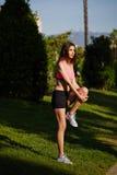 Sportowy żeński jogger robi rozciągania ćwiczeniu w parku na zielonym tle z drzewami Zdjęcia Stock