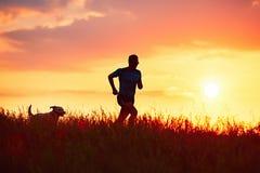 Sportowy biegacz z psem przy zmierzchem zdjęcia stock