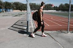 Sportowy facet w kapitałce ubierał w czarnym sporcie odziewa z plecakiem na jego ramię spacerach wzdłuż boiska ogrodzenia obraz royalty free