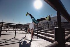 Sportowy facet z kapitałką na jego głowie ubierającej w białej koszulce, czarnych leggings i błękitnych skrótach, robi sztuczce fotografia royalty free
