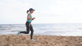Sportowy kobieta bieg wzdłuż plaży swobodny ruch zbiory wideo