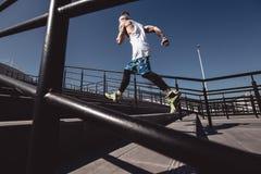 Sportowy mężczyzna z kapitałką na jego głowie ubierającej w białej koszulce, czarnych leggings i błękitnych skrótach, jest działa obraz stock
