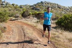 Sportowy mężczyzna jogging na kraju śladzie zdjęcie stock