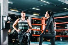 Sportowy m??czyzna opowiada sport kobieta w gym Sprawno?? fizyczna trening Komunikacja mi?dzy lud?mi zdjęcia stock