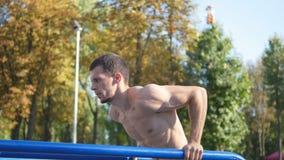 Sportowy mężczyzna podnosi na równoległych barach przy sportami mlejącymi w miasto parku robić pcha Silny młody mięśniowy faceta  Fotografia Royalty Free