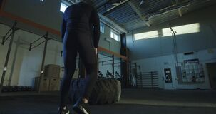Sportowy mężczyzna podrzuca ciężką samochodową oponę zdjęcie wideo