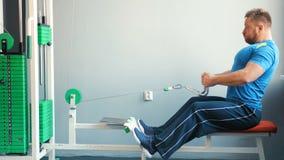 Sportowy mężczyzna pracujący na symulancie w stażowym gym out zbiory