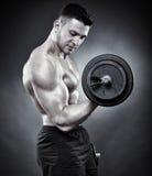 Sportowy mężczyzna pracujący z ciężkimi dumbbells out Fotografia Stock