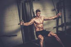 Sportowy mężczyzna robi ćwiczeniom na stażowym aparacie przy gym studiiem obrazy royalty free