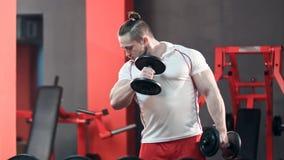Sportowy mężczyzna robi ćwiczeniu z dumbbells w gym Zdjęcia Royalty Free