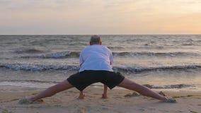 Sportowy mężczyzna robi ranku rozciąganiu na piasek plaży blisko morza z fala zdjęcie wideo