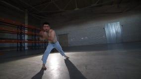 Sportowy mężczyzna robi trudnym capoeira elementom w pokoju z betonem - koziołkuje nad jego głową bez ręk - zbiory wideo