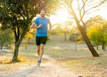 Sportowy młodego człowieka bieg w naturze przy zmierzchem w jesieni w sprawności fizycznej Zdrowym styl życia obrazy royalty free