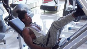 Sportowy młody Afrykański mężczyzna opracowywa na nogi prasy maszynie przy gym zbiory