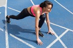 Sportowy młody biegacz na zaczyna linii przy bieg śladu stadium Zdjęcia Stock