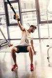 sportowy młody człowiek ćwiczy z zawieszenie patkami w sportswear fotografia stock