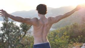 Sportowy, przystojny dysponowany młody człowiek plenerowy w kraju robi rozciąganiu, ćwiczy zdjęcie wideo