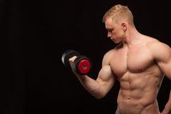 Sportowy przystojny mężczyzna model jest pracujący z dumbbell i seansem out jego perfect ciało Odizolowywający na czerni Zdjęcie Royalty Free