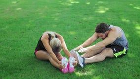 Sportpaar de oefening van de opleidingsrek op groen gras in de zomerpark stock videobeelden
