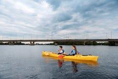 Sportpaar die rode en gele peddels houden roeiend in kano stock foto's