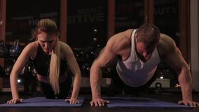 Sportpar som gör push-UPS i idrottshallen lager videofilmer