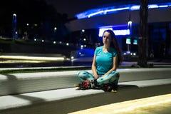 Sportrollenmädchen, das in einer Lotoshaltung nach der Ausbildung sitzt Lizenzfreies Stockbild