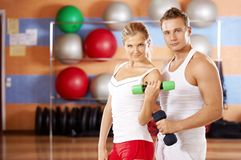 Sports. Pair of sportsmen with dumbbells in hands in sports club Stock Images