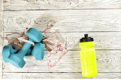 Sports accessories. Dumbbells, bottle, centimeter tape. Royalty Free Stock Photography
