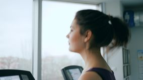 Sports activities, happy girl running on treadmill in gym close-up. On background window stock video