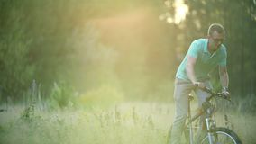 Sports activity, young adult cyclist riding mountain bike in the countryside. Man, athlete, bicycle. The young man rides stock footage