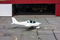 A sports airplane near an open hangar in which there is a small helicopter. A sports aircraft near an open hangar in which there is a small helicopter Stock Image
