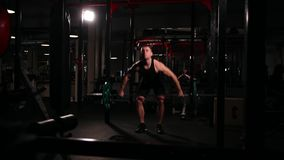 A sports athlete in the gym raises the bar with a weight above his head from the sitting position. A sports athlete in the gym raises the bar with a weight stock footage