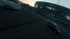 Sports cars drive drifting on empty plain road in night city