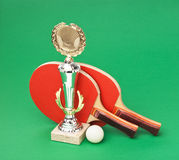 Sports awards and  tennis racquets on  green table. Sports awards and  tennis racquets on a green table Royalty Free Stock Photography