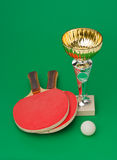 Sports awards and  tennis racquets on  green table Stock Image